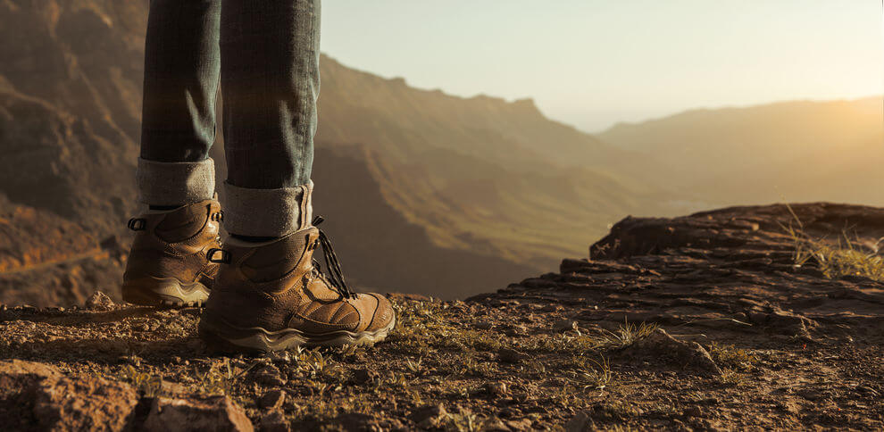 close up of hikers boots enjoying the sunset