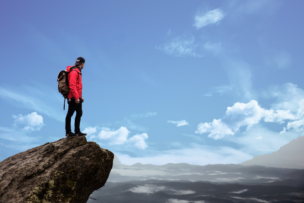 man hiking on mountains with small backpack