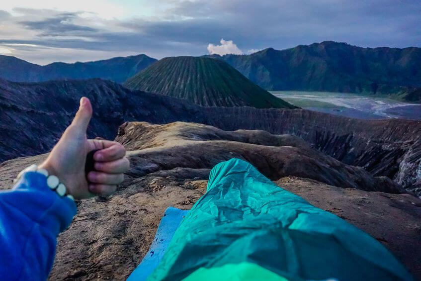 man in a 3 season sleeping sleeping bag on the ridge of volcano