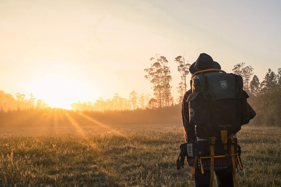 man with large backpack hiking early at morning