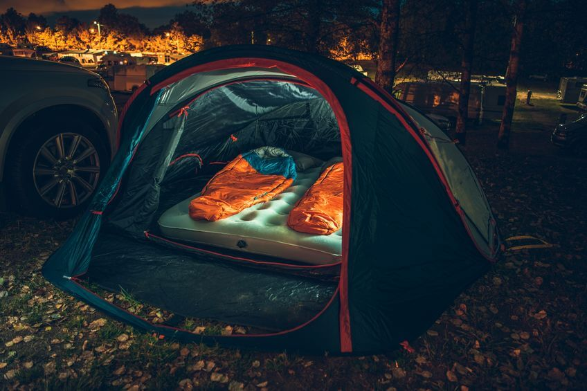 sleeping bags inside camping tent close to car