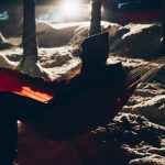 woman sitting in camping hammock under the trees at winter night