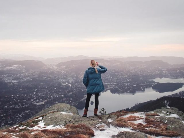 woman wearing backpaking jacket and standing on top of mountain