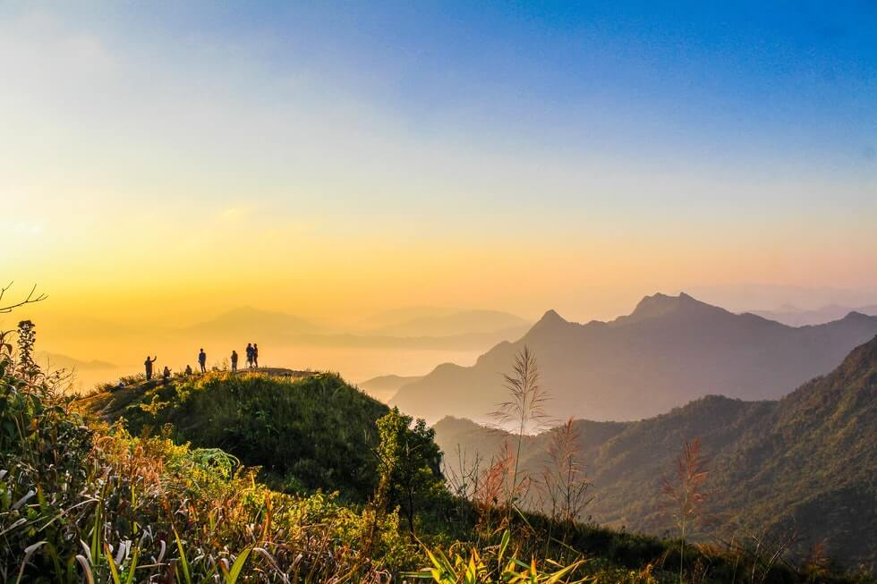 backpacker standing on top of mountain during golden hours