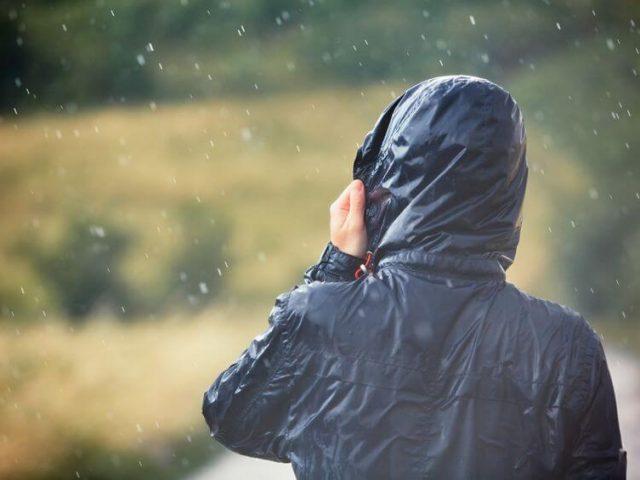backpacker wearing rain jacket walking in nature during heavy rain