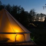 glamping canvas bell tent glows at night at forest