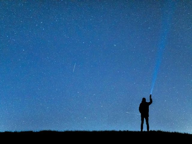 hiker holding flashlight and looking at night sky
