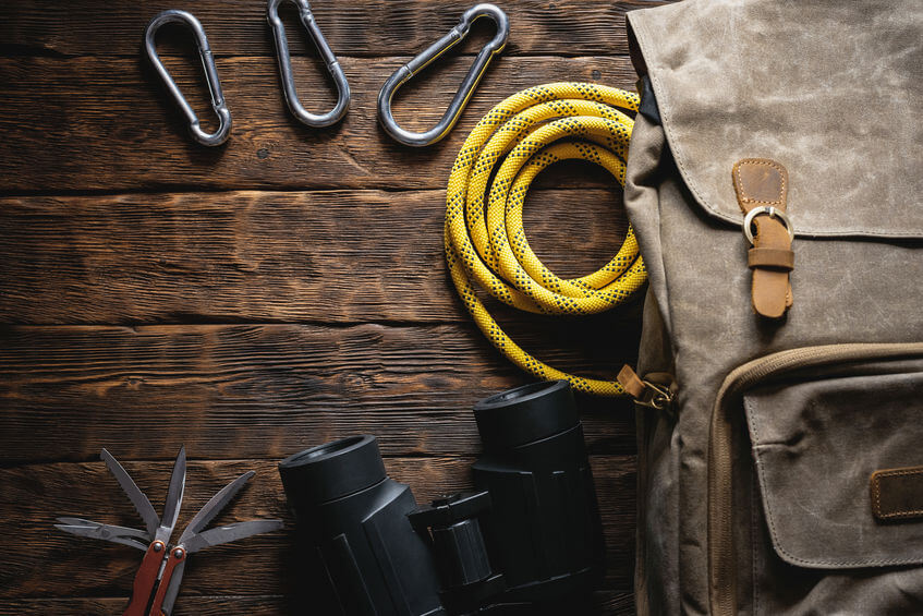 hiking backpack, multitool knife, rope and carbines on wooden table