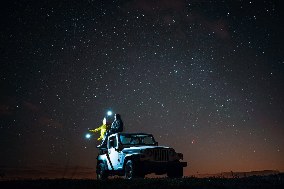 travelers looking at stars in the night