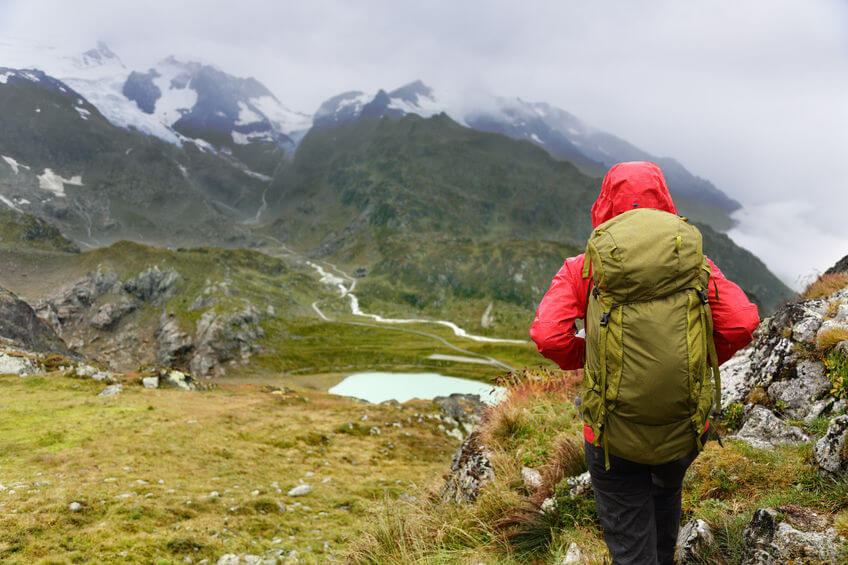woman on trek with backpack and jacket walking on hike in mountain
